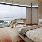magnificent beach house with wonderful stone walling and elegant wall mounted fireplace with large glass window overlooking the sea view also cozy low profile bed in laminate flooring