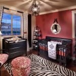 magnificent girl nursery room with black teak wood crib and gorgeous flowery patter armchair and interesting zebra motif rug with round hang mirror in laminate flooring