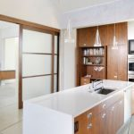 magnificent kitchen desin with brown and white accent feat trasnculent sliding frosted glass door feat large cabinet in white tiling concept