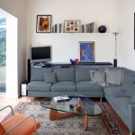 minimalist Dwelling Room decorations Triangle Glasses Table On Rug That includes Gray Couch As Effectively Body On The Wall Decoration And Television Nook