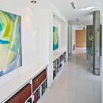 modern hallway white wall white ceiling white ceramic floor white open bookshelves abstrack paintings gold downlights grey posts blue tinted glass table glass vase