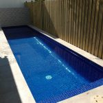 moziaic tiled pool floor long and slender lap swimming pool porcelain tiled pool side wooden enclosures small swimming pool idea