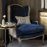 navy elegant armchair with gold frame gold patterned cushion gold round table white vase gold an white striped wall gold cabinet white rug with navy border