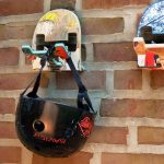old skateboards with various pictures in it and some scratches funky skatehook wall hook double-headed hook black bicycle helmet raw brick wall