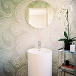 patterned wallpaper white pedestal sink round unframed mirror white base molding wooden floor potted white orchid bathroom plant options beautiful vanity area