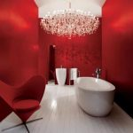 red painted wall red uphosltered swivel chair white ceramic tile flooring white painted ceiling dramatic chandelier white freestanding battub white sink single steel faucet steel towel hanger