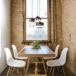 rustic wooden floor brick wall white painted wall wooden varnished dining table white dining chairs metal pendant lamp wooden framed window potted flowers industrial dining room
