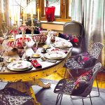 silver curtain yellow wood framed winow red container light grey dining chairs black and red cushions gold candelabra white and red plate set hardwood flooring yellow round dining table with wood counter