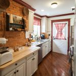 sophisticated white cabinet wood countertop white ceiling with dark brown trim raw brick wall steel undermount sink white doow blocked red-white curtain downlights diagonal wood floor