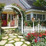 stone and grass pathway white picket  fence with white arched entrance yellow wall red wood door red rocking chair white framed window climbing rose beautiful garden