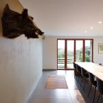wall mounted animal's head gray white painted wall white painted ceiling wooden long table black chairs wooden windor frame gray ceramic tiled floor cozy holiday house design