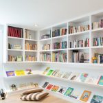 white ceiling white wall white open bookshelves light brown carpet flooring downlight brown-white stripped cushions white blind various books long white shelves