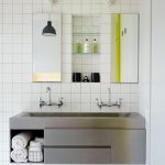 white ceramic tiled wall white ceramic tiled floor metal integrated sink metal bathroom counter unframed mirror simple black pendant lamp white door double faucet mininalist vanity area design