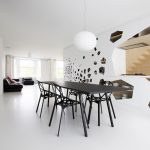 white concrete floor white painted wall white painted ceiling black minimalist dining table black minimalist dining chairs black leathered couch white round pendant lamp minimalist furniture