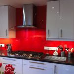 white gloosy kitchen cabinets black marble kitchen countertop steeled smoke sucker steeled bread toaster steeled water heater red colored glass splashback glass splashback design