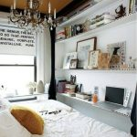 white large bed white painted wall crystal chandelier brown painted ceiling four leveled shelves brown knitted cushion abstract pictures a group of books