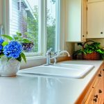 white marble kitchen countertop white painted kitchen cabinet beautiful flowers in pot green leafy plant in rattan white drop in sink steeled faucet healthier and greener kitchen