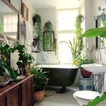 white mozaic tile floor white mozaic tile wall black painted vessel bathtub wall mounted sink wooden varnished bathroom cabinet potted tropical plants green bathroom bathroom plant options