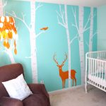 white mural tree with orange deer and bird blue wall dark brown armchair white cushion with letters pattern white crib white ceiling brown rug white-orange contemporary hanging lamp