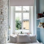 white painted brick wall light blue painted wall white bedspread white pillows white rolling curtain small pendant lamp white hanging shelves white painted ceiling a group of books