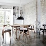 white painted brick walls white painted ceiling dark concrete floor wooden varnished dining table wooden varnnished dining chair black metal pendant lamp white painted wooden open storages