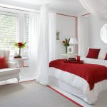 white painted wall white ceramic floor white painted ceiling white cozy armchair white bedsheet red bedspread white cushions round unframed mirror gray bedroom rug