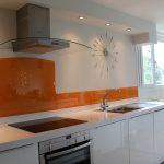 white painted wall white gloosy kitchen cabinets white glossy kitchen countertops steeled undermount sink white painted ceiling trendy wall clock orange glass splashback glass splashback design