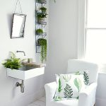 white painted wall white upholstered armchair white painted wooden floor white vessel sink metal bathroom shelves leafy patterned cushion potted fern and leafy plants bathroom plant options