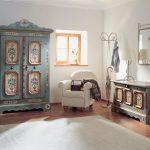 white painted wall wooden floor white simple rug wooden framed window light blue vintage wardrobe white upholstered armchair light green vintage chest vintage desk lamp vintage styled theme