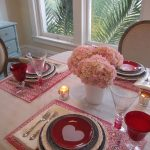 white table cloth red patterned table mats unique drinking glasses red drinking glass love shaped patterned plate a bucket of pink flowers wooden creame upholstered armchairs