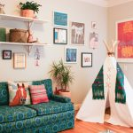 white teepee with green decor white hanging shelves beige wall with white trim retro green-blue sofa hardwood flooring horse printed cushion framed textiles
