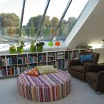 white wood flooring wide skylight colorful striped beanbag chair brown armchairs colorful pillows white open bookshelf green vases white ceiling orange table lamp green table lamp white table lamp