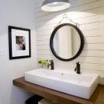 white wooden varnished wall white painted wall wooden varnished panel white long vessel sink double faucet round black framed mirror black framed photo gray wall sconce lamp  rustic stool