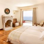 wonderful elounda peninsula hotel with amazing uniquely designed room with elegant white ming size bed also gorogeus stone fire place with open window design overlooking sea view in laminate flooring