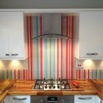 wooden varnished kitchen countertop white kitchen cabinets steeled smoke sucker colorful striped glass splashback glass splashback design
