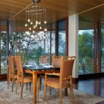 beige patterned rug brown wood dining chairs glass and wood dining table floor to ceiling windows with wood frame brown concrete flooring amazing crystal hanging lamps wood ceiling
