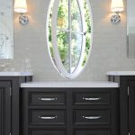 black cabinet with iron handles and white counter light grey tiled wall white tiled flooring white sconces square simple mirrors white ox eye window with vertically opened pivot