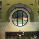 black ceramic counter stainless metal undermount sin white wall olive green curved upper cabinet white ox eye windows with black frame stainless faucet