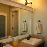 Black Sconces Colorful Striped Towel White Sink Beige Tiled Counter Dark Brown Cabinet Wide Mirror With Grey Frame White Door Yellow Container Colorful Towels Chalkboard Wall Decoration Mint Green Wall