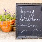 chalkboard accessory in gothic style frame clay-made pot with beautiful flowers