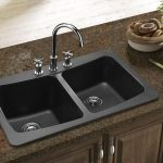 composite granite kitchen double sinks with stainless steel faucet and double sprayer controls dark gray marble countertop cabinet system under the sink decorative green plants