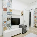 cool apartment design with small wall mount tv and long drawer with eclectic colorful mosaic tile on the wall in laminate flooring