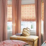 corner bay window woth floor-to ceiling curtains and orange rods curtains setee furniture  in yellow color red bedcover with beautiful prints