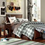 dark wood side table dark wood bed grey white green striped rug hardwood flooring white wall black table lamp white framed window grey bed sheet brown baskets white and black bicycle brown clay pot
