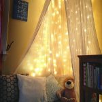 dramatic reading area with cozy nook and elegant transparent curtain with alluring yellow wall with small book shelve
