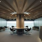 eclectic office design with futuristic wavy ceiling and elegant round table for work with black accent in large concrete flooring