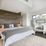 elegant white bedroom with soft fur rug also large king bed with earty wooden wall panel also interesting wooden cabinet in laminate flooring