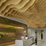 fantastic hotel loby design with wonderful wooden wavy ceiling and interesting brown wall panel with green fresh element in concrete flooring