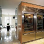 giant fridge with ravishing round table for dining and elegant white wall with large cabinet in tile flooring