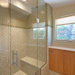 glass shower door wood vertical cabinets beautiful shower tiles  round ceiling lighting simple modern bathroom design